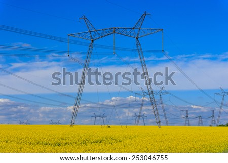 high voltage power line on rape field  - stock photo
