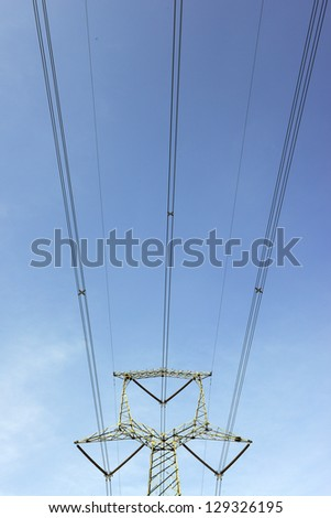 High voltage power line tower in the blue sky in the background