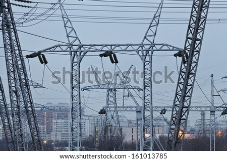 High-voltage power lines against a city landscape in twilight