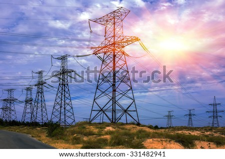High-voltage power lines against the background of a clouds  with the sun - stock photo