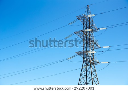High voltage power lines against the blue sky - stock photo