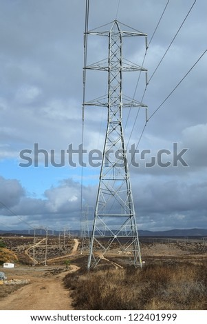 High voltage power lines and access road stretch across the California high desert toward the stormy Sierra Nevada Mountains