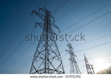 High voltage power lines at dusk. - stock photo