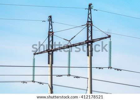 high-voltage power lines in a field on a summer day  - stock photo