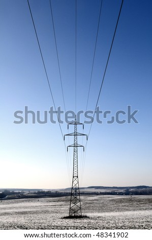 High voltage power lines in a winter landscape - stock photo
