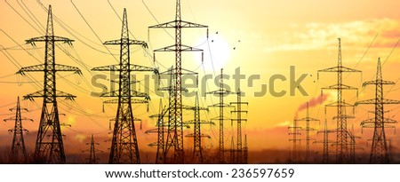 High-voltage power lines in an industrial area .On background sunrise. - stock photo