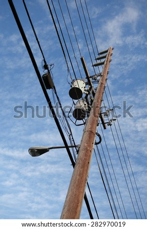 High Voltage Power Lines line wooden Utility pole with blue cloudy sky on Oahu, Hawaii. - stock photo