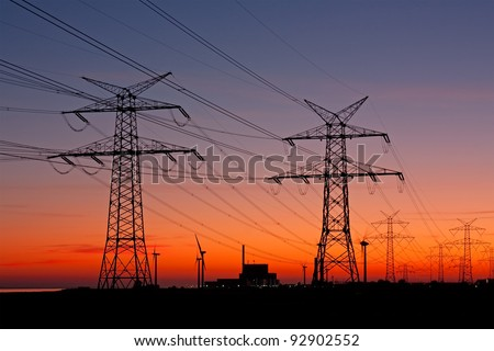 High voltage power lines with electricity pylons at twilight. At the horizon a nuclear power plant and wind turbines. - stock photo