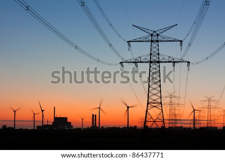 High voltage power lines with electricity pylons at twilight. At the horizon wind turbines and a nuclear power plant. - stock photo
