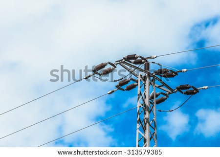 high voltage power pylons against blue sky  - stock photo