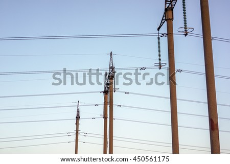 High voltage power pylons against blue sky. High voltage power towers against blue sky on sunset - stock photo