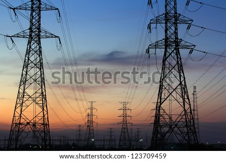 High voltage power pylons in twilight - stock photo