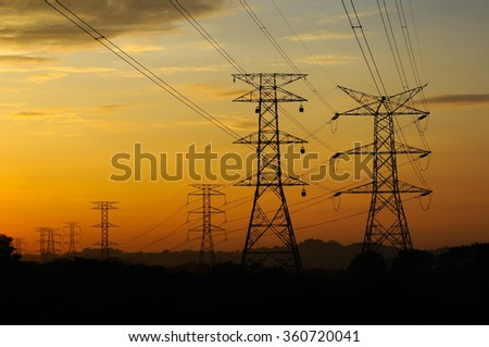 High voltage power tower and power lines sunset - stock photo