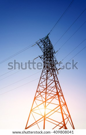 High voltage power tower on blue background. Energy line on clear blue sky back.