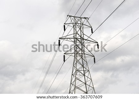 high voltage power tower under cloudy sky