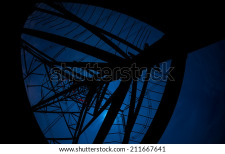 High-voltage power transmission pylons towers during night sky background - stock photo