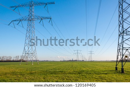 High voltage pylons and power lines to the power station in the background with smoke from the chimneys. - stock photo