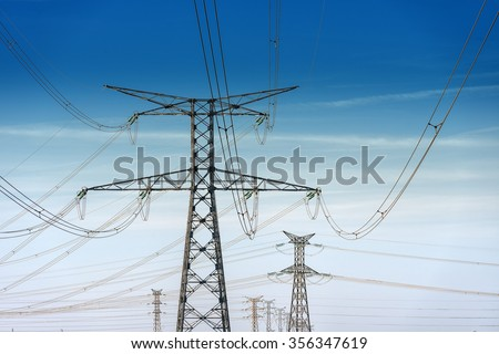 high voltage pylons on blue cloudy sky background - stock photo