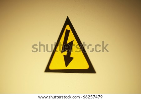 High voltage sign hung on yellow background.