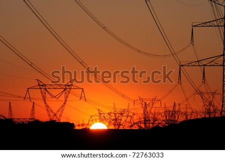high voltage steel transmission tower during sunset - stock photo