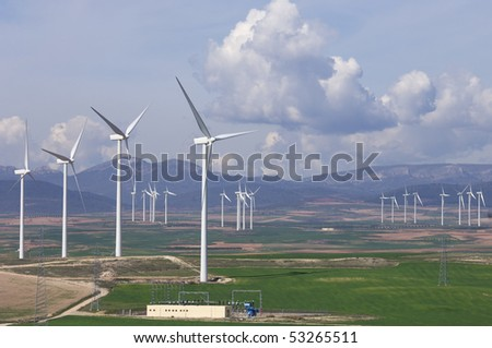 high voltage substation and windmill with cloudy sky - stock photo