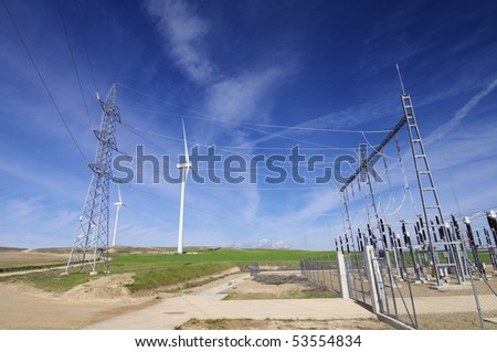 high voltage substation and windmills with cloudy sky - stock photo