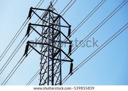 High-voltage tower and electric lines over blue sky