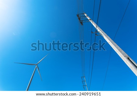 High-voltage tower and turbine machine wite blue sky background. - stock photo