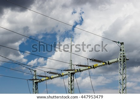 High voltage tower (electricity post) against blue sky with white clouds - electric distribution from transformer station. - stock photo