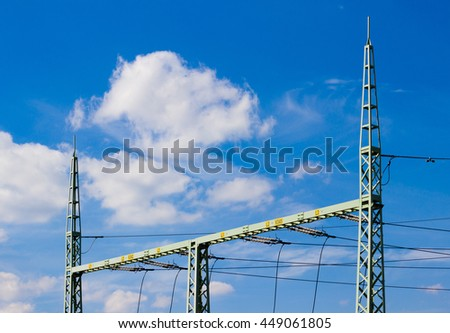 High voltage tower (electricity post) against blue sky with white clouds - electric distribution from transformer station - stock photo