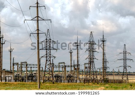 High voltage tower on a lot of down-junction power station on a background cloudy sky - stock photo