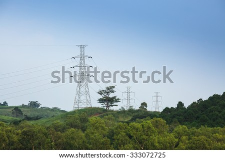 High voltage tower on green mountain - stock photo