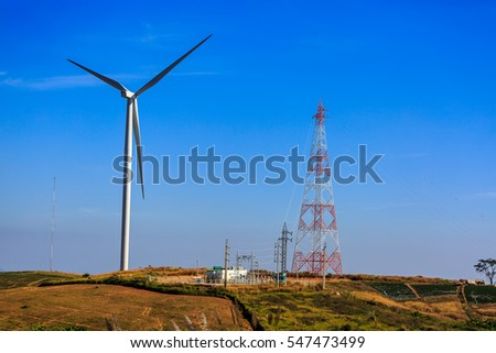 High voltage tower , station distribution and wind turbine with blue sky background