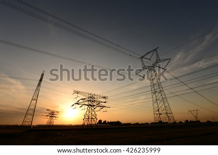 High voltage towers under the setting sun
