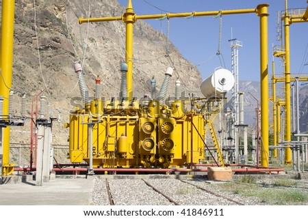 High voltage transformer at power plant. Mountain and blue sky - stock photo
