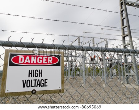 High-voltage transformer substation behind barbed-wire chain-link fence with Danger High Voltage sign. - stock photo
