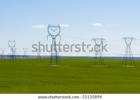 High voltage transmission line stretching over the rolling hills - stock photo