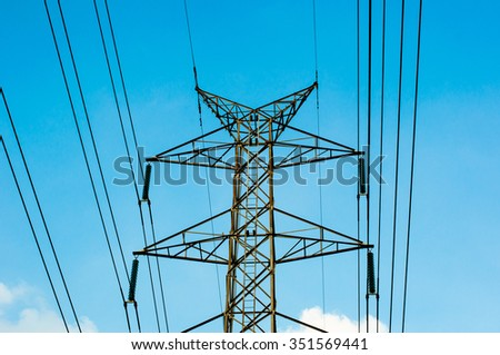 High voltage transmission lines isolated on blue sky background - stock photo