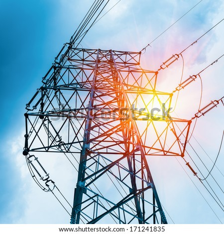 high voltage transmission pylon closeup and sun rays  - stock photo