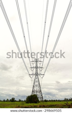 High voltage transmission tower on the ground with gray clouds background. - stock photo