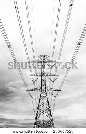 High voltage transmission tower with clouds background.Used color tool for black and white tone. - stock photo