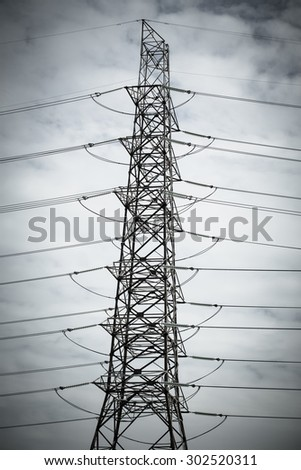 High voltage transmission tower with clouds. electricity post color tool for black and white tone. - stock photo