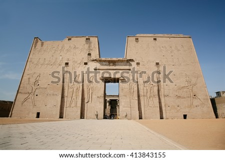 high wall front facade of Egyptian Edfu Temple of falcon god Horus, with carving figures and hieroglyphs, in Egypt, Africa - stock photo