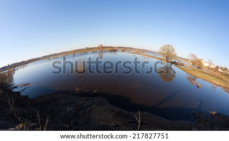 High water (flood, overflow) by a Spring time in the Klyazma river near Vladimir (Russia) with trees, lawns and roads underwater. SHot with a fish-eye lens. - stock photo