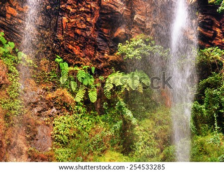 High waterfall in red rock cliff, tropical African rainforest - stock photo