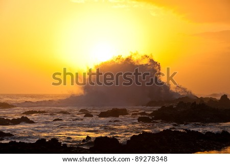 High wave breaking on the rocks at sunset - stock photo