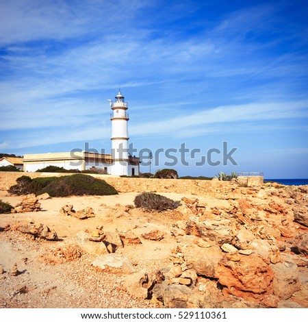 High white lighthouse on a rocky sea coast on Majorca island