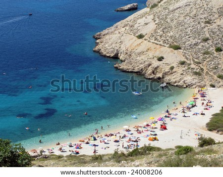 High wide angle shot of an Adriatic bay crowded with tourists on the beach. Island Krk. Croatia.