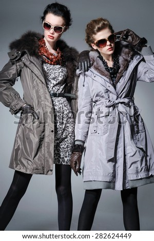high young attractive two girl wearing fur coat on gray background  - stock photo