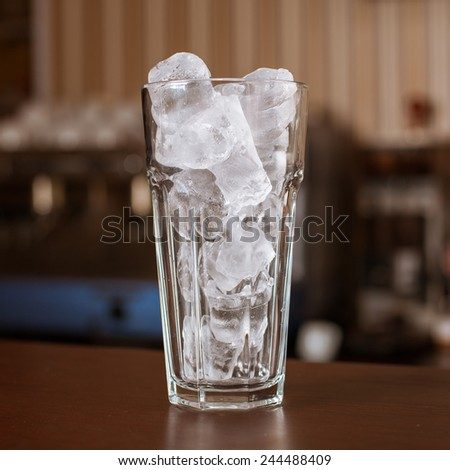 highball glass with ice and a yellow tube on the wooden bar - stock photo